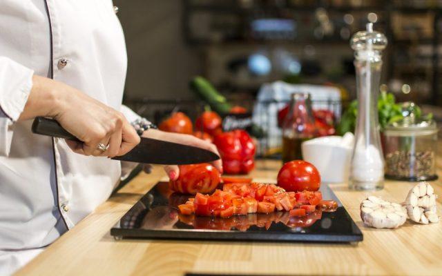 Kucharz krojący na desce z kamienia